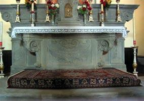 Altare maggiore costruito in pietra serena nell'anno 1762; presenta ai lati due volute ripetute nei sostegni della mensa